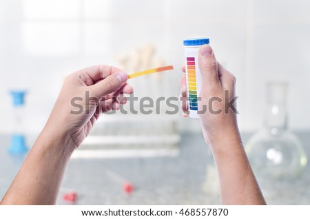 Scientist working colored litmus paper in hand in a lab, first-person, on a light background research lab, chemist in the lab examines a sample of contamination