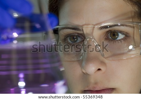 scientist working in her laboratory examining an experiment - stock photo