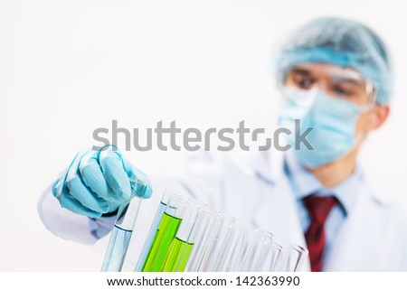 scientist working in the lab, in protective mask and cap, examines a test tube with liquid - stock photo