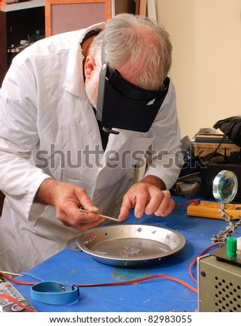 Scientist working on a secret project in his lab - stock photo