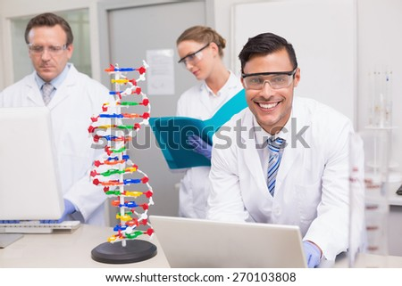 Scientist working together with laptop and computer in laboratory - stock photo