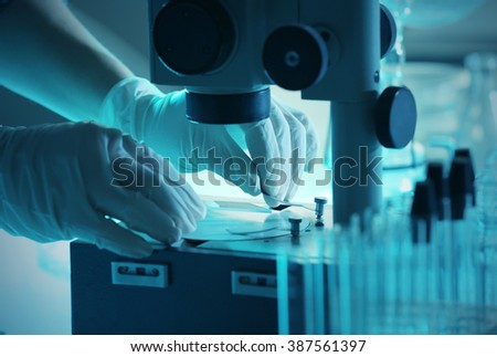 Scientist working with microscope closeup