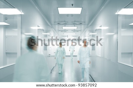 Scientists and doctors at modern pharmaceutical factory - stock photo