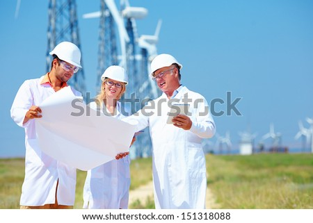 scientists discussing project on wind power station - stock photo