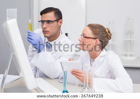 Scientists examining yellow precipitate in tube in the laboratory - stock photo