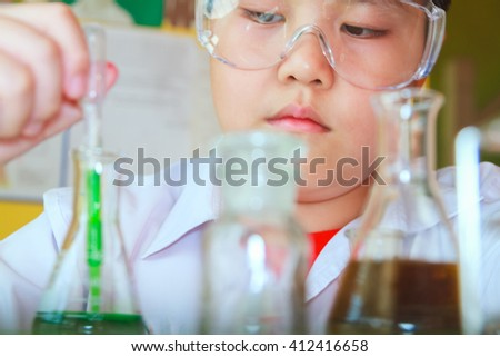 Scientists junior is a very happy or fun to make and play chemical science experiment in science class, copy space, mock-up, web template for design or decorate your content, Asia boy.
