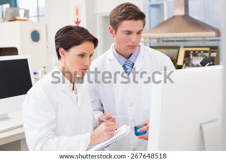 Scientists looking attentively at computer in laboratory - stock photo