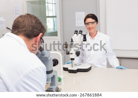 Scientists looking attentively in microscopes in laboratory