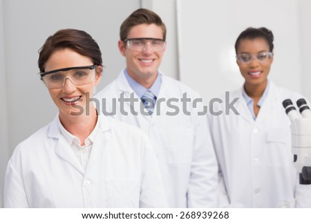 Scientists smiling and looking at camera in laboratory - stock photo