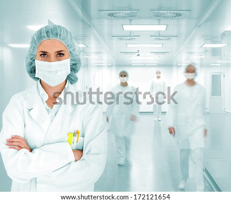 Scientists team at modern hospital lab lead by a woman doctor - stock photo