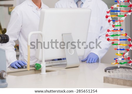 Scientists working on laptop together in the laboratory