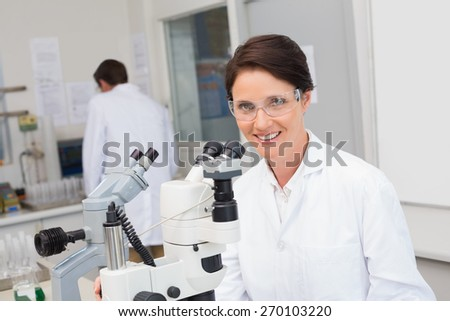 Scientists working with microscope and computer in laboratory - stock photo