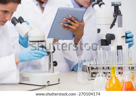 Scientists working with microscope and tablet in laboratory - stock photo