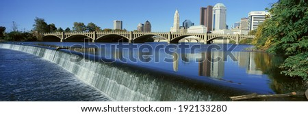 Scioto River with waterfall and Columbus Ohio skyline, with setting sunlight - stock photo