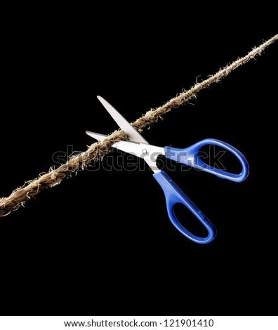 Scissor cutting a rope on black background. - stock photo