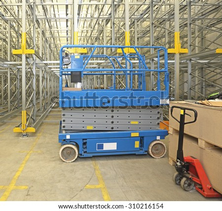 Scissor Lift Aerial Work Platform in Distribution Warehouse - stock photo