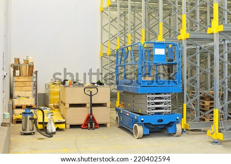 Scissor lift at construction site in distribution warehouse - stock photo