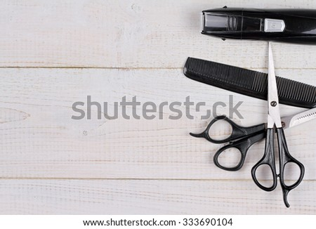 Scissors and comb  on white rustic wooden background. Hairdresser salon concept. Haircut  accessories