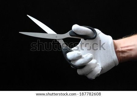 Scissors and Hand on a Black Background - stock photo