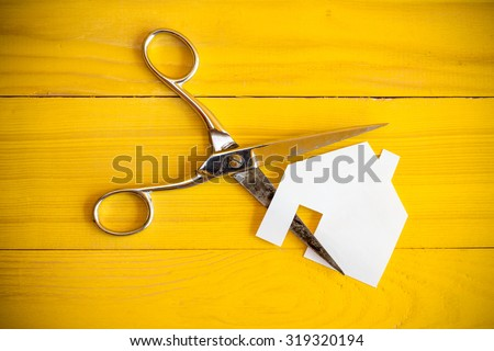 Scissors and house cut out of paper on the yellow background