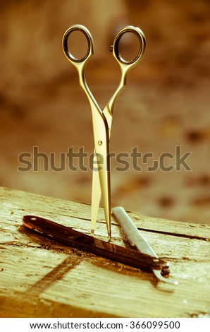Scissors and razor on a wooden beam