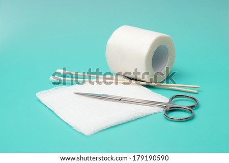 Scissors and wound dressing supplies on aqua background. - stock photo