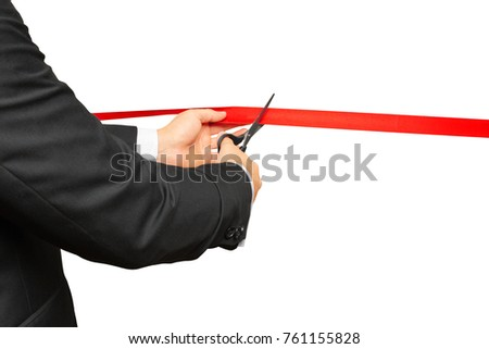Scissors are cutting red ribbon or tape. Isolated on white background.