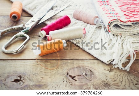 Scissors, bobbins with thread and needles, striped fabric. Old sewing tools on the old wooden background. Vintage Background toning