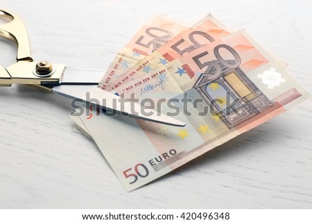 Scissors cuts euro banknote on table - stock photo