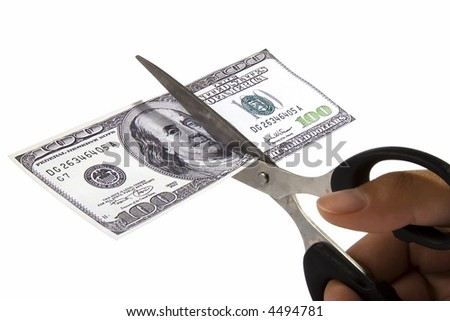 Scissors cutting an one hundred dollar note. - stock photo