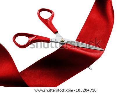 Scissors cutting red silk ribbon on white background - stock photo