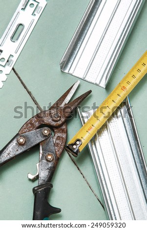 Scissors for metal and measure tape on  plasterboard  - stock photo