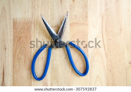 Scissors on the Wooden Background
