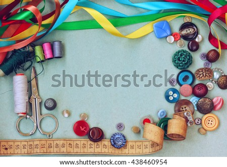 scissors, thread, needle, thimble, variety buttons, measuring tape and silk ribbon on old gray cardboard table - stock photo