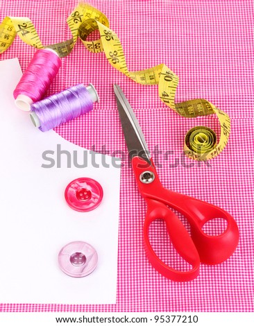 Scissors, threads, buttons, measuring tape and pattern on fabric isolated on white - stock photo