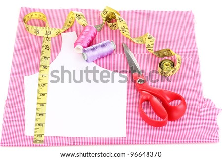 Scissors,threads, measuring tape and pattern on fabric isolated on white - stock photo
