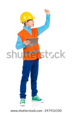 Scolding little construction worker. Young boy in yellow hard hat and orange reflective vest holding a digital tablet, shouting and rising fist. Full length studio shot isolated on white. - stock photo