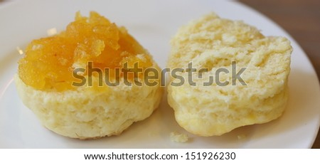 Scone with fresh cheese and orange jam - stock photo