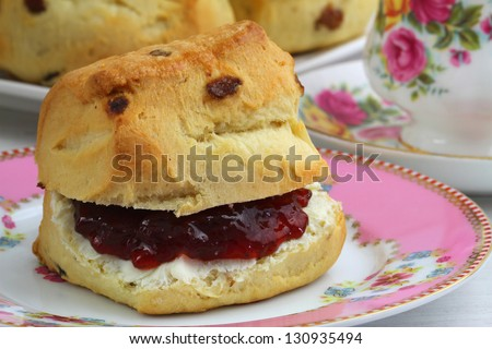 Scone with strawberry jam and clotted cream, close up - stock photo