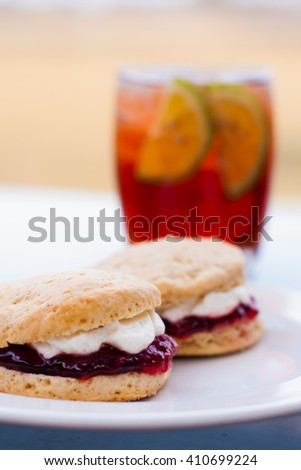 Scones with clotted cream and strawberry jam with ice tea in the background - stock photo