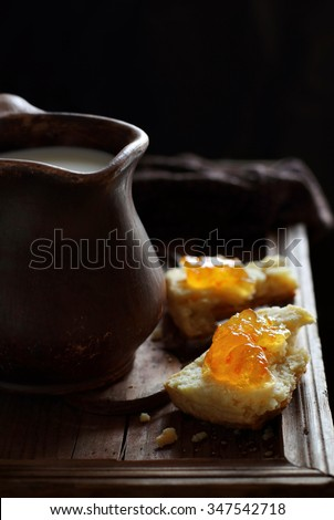 Scones with orange marmalade and a jug of milk against backlight. Taken with natural light. - stock photo
