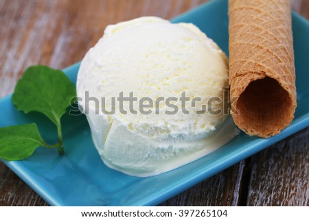 Scoop of home made creamy vanilla ice cream and crispy wafer, closeup  - stock photo