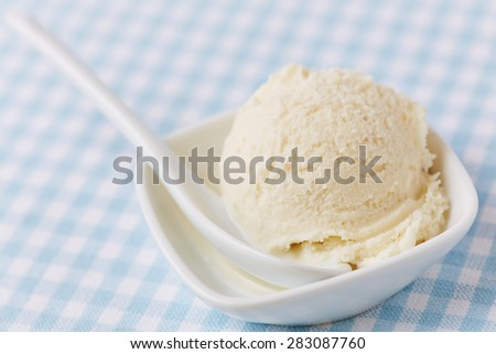 Scoop of homemade vanilla ice cream with spoon in a bowl