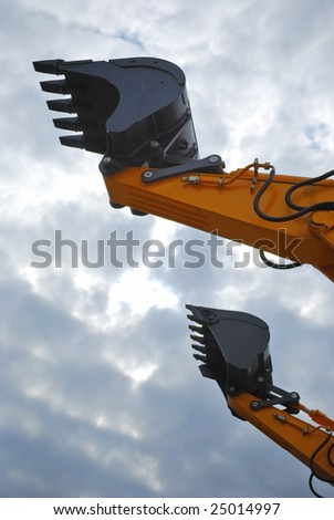 scoop of power-shovel is on cloud sky - stock photo