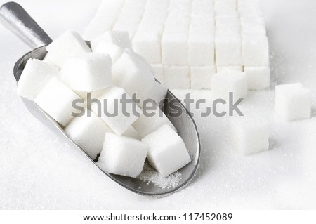 scoop of  sugar cubes on white background