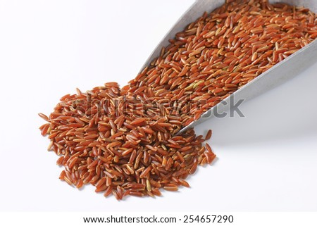 Scoop of uncooked red rice - stock photo