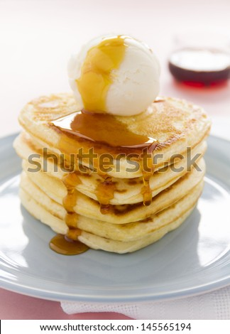 Scoop of vanilla ice cream on a heart shaped pancakes with dripping maple syrup.
