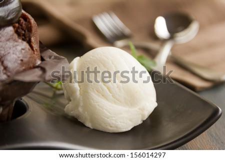 Scoop of vanilla ice cream with a chocolate muffin ready to serve.