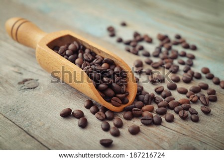 Scoop with coffee beans on wooden background closeup - stock photo