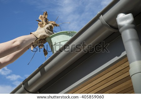 Scooping leaves from gutter into bucket during Autumn - stock photo
